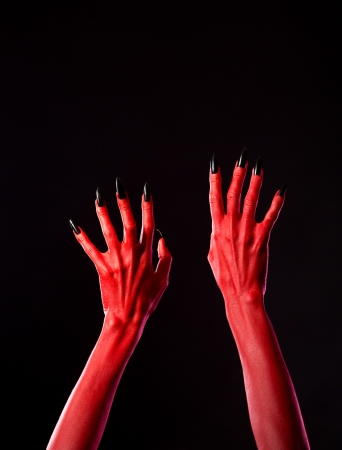 Red spooky devil hands with black nails, Halloween theme, studio shot on black background  photo