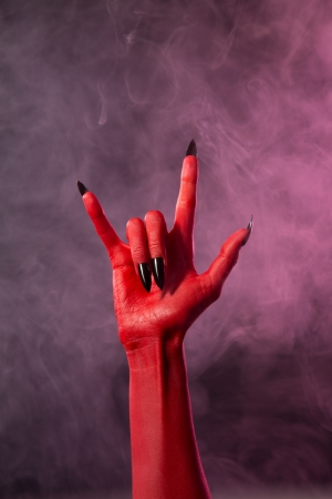Heavy metal, red devil hand with black nails, studio shot on smoky background