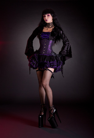 Sexy young woman in black and purple costume wearing extra high heels   photo