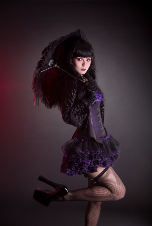 Portrait of gothic Lolita girl with umbrella, studio shot on black background  photo