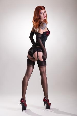Achter mening van een mooie roodharige pin-up stijl jonge vrouw, studio opname op witte achtergrond
