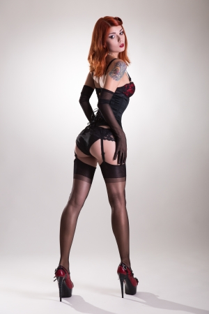 Rear view of a beautiful redhead pin-up style young woman, studio shot on white background
