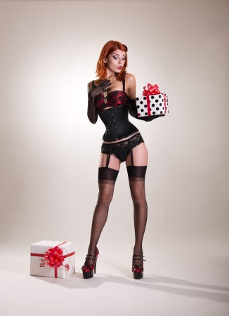 Beautiful redhead pin-up style girl holding gift box, Christmas or holiday theme  Reklamní fotografie