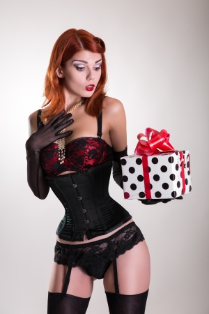 Portrait of a beautiful redhead pin-up style girl holding gift box, Christmas or holiday theme  photo