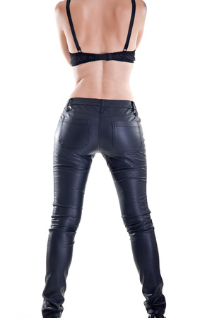 Rear view of a girl in tight leather pants, isolated on white background  photo