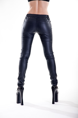 Long legs in skinny leather pants and high heels, studio shot on white background  photo