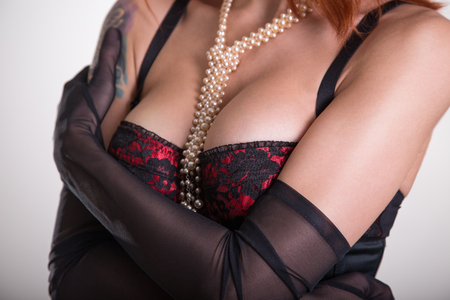 Close-up shot of a busty woman in vintage red bra, sheer gloves and pearl necklace   photo