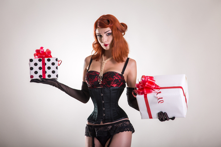 Portrait of pretty redhead pin-up girl holding gift boxes, Christmas or holiday theme  photo