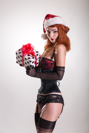Pinup girl in Santa Claus hat, holding gift box, Christmas theme  photo