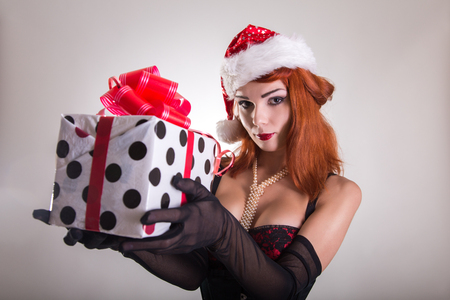 Pretty redhead pin-up girl in Santa Claus hat holding gift box, Christmas or holiday theme  photo