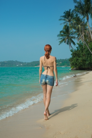 Beautiful girl walking on the tropical beach with palm trees  Stock Photo