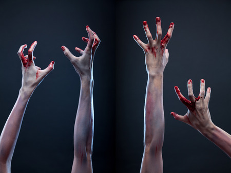 不気味な一連の流血のゾンビの手、灰色の背景にわたって撮影スタジオ