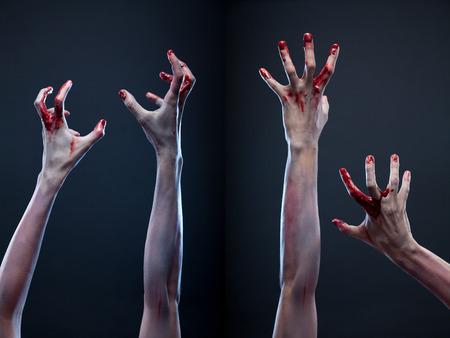 Griezelige reeks bloederige zombie handen, studio-opname over grijze achtergrond