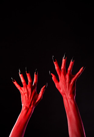 diabolic: Red devil hands with black nails, Halloween theme, studio shot on black background