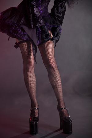 fishnet stockings: Gothic girl putting on stockings, studio shot on smoky background  Stock Photo