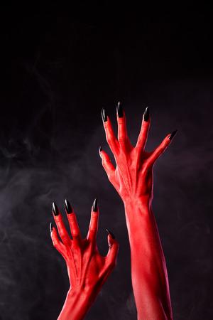 monster hand: Horror red devil hands with black nails on smoky background, studio shot
