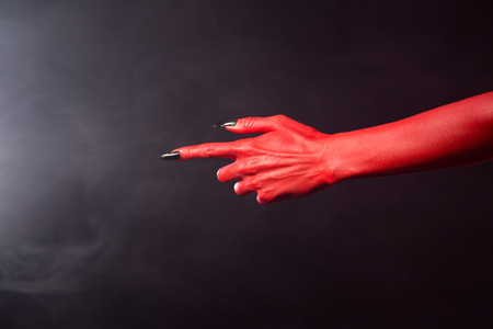 index finger: Red devil pointing hand with black sharp nails, extreme body-art, Halloween theme   Stock Photo