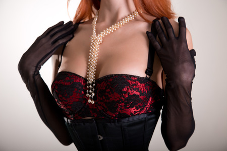 Close-up shot of a busty redhead woman in vintage red bra and sheer gloves, studio shot  photo