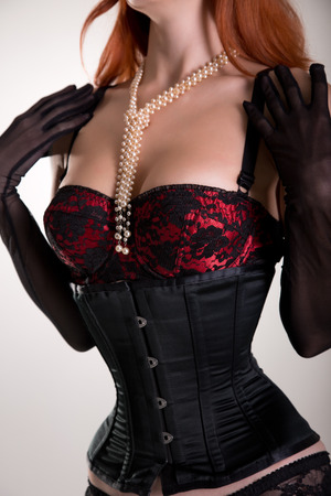 Busty redhead woman wearing corset, vintage red bra and sheer gloves, studio shot  Stock Photo