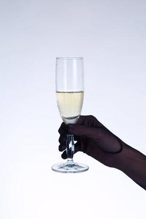 Female hand in black opera glove holding champagne glass, studio shot on gray background   photo