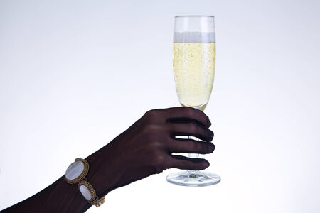 Close-up shot of female hand in black opera glove holding champagne glass, studio shot  photo
