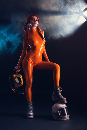 Sexy girl in orange latex catsuit with helmet and camera, sci-fi setting  photo