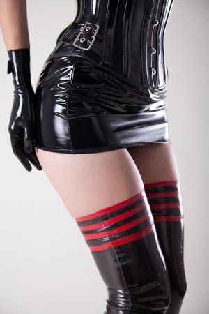 Sexy girl dressed in fetish outfit, corset, latex stockings and skirt   photo