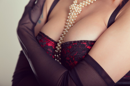 Busty woman in vintage red bra, sheer gloves and pearl necklace   photo