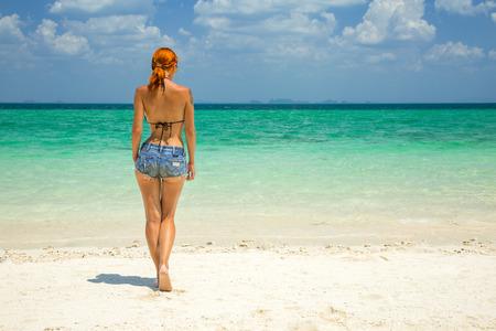 Mooie roodharige vrouw op het tropische strand met turquoise water en wit zand Stockfoto
