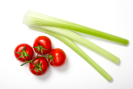 top angle: Top view of bunch of fresh tomatoes and celery sticks on white background
