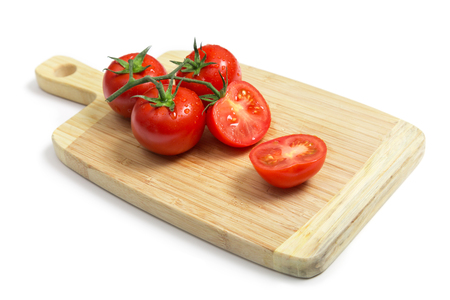 Fresh tomatoes on wooden chopping board, isolated on white background with shadow  photo