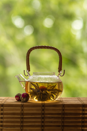Transparent teapot with blooming tea flower on green natural background  photo