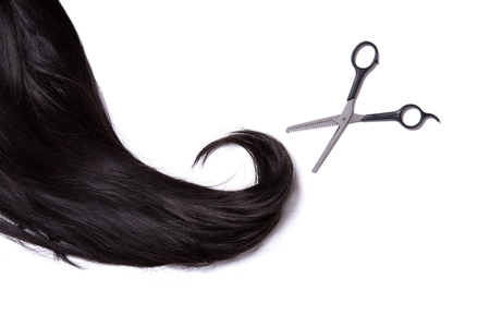 strand of hair: Long black shiny hair with professional scissors, isolated on white background