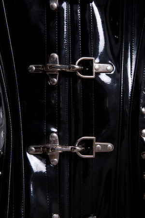 Close-up shot of metal clasps on black leather corset  photo