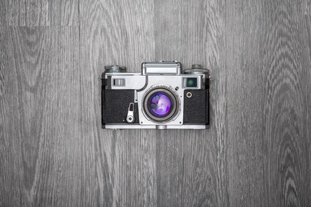 Old retro camera on grey wooden background  photo