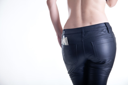 topless jeans: Rear view of young woman in leather pants with dollars in pocket  Stock Photo