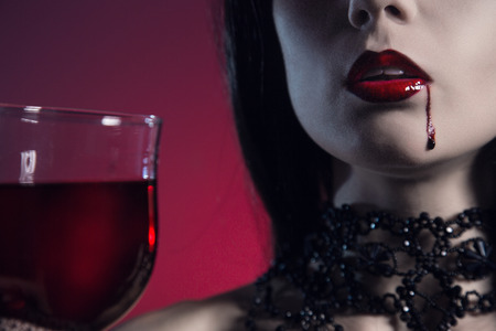 Sexy vampire girl with glass of wine or blood, studio shot  photo