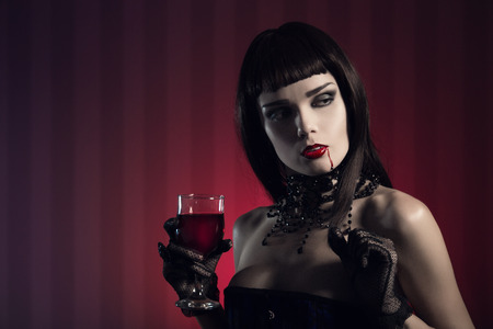 Dangerous sexy vampire girl in glamorous outfit with glass of wine or blood  photo