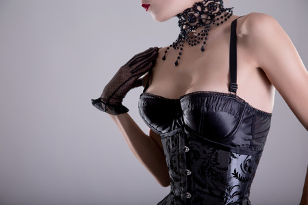 Close-up shot of elegant young woman in silver corset and bead jewelry, studio shot  photo