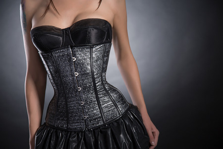 Close-up shot of young woman wearing silver corset with stars, studio shot  photo