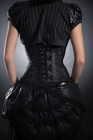Gothic style: Back view of woman wearing black rose corset and Victorian style outfit, studio shot