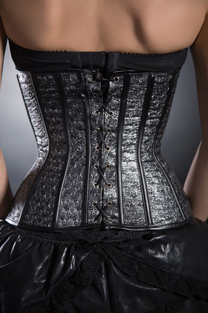 gothic fetish: Back view of woman wearing silver leather corset with stars pattern, studio shot