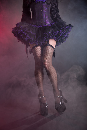 Sexy female legs in fishnet stockings and high heel shoes, studio shot on smoky background  photo