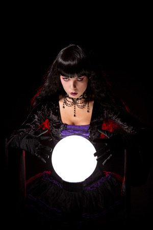 Beautiful witch or fortune teller with a crystal ball, Halloween theme   photo