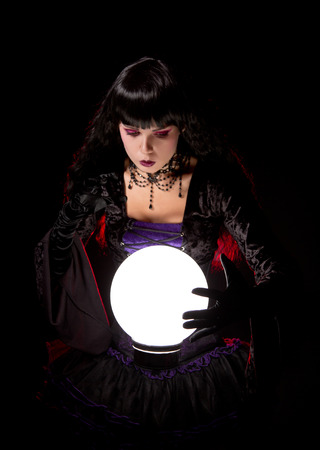 gazer: Attractive witch or fortune teller looking into a crystal ball, Halloween theme   Stock Photo