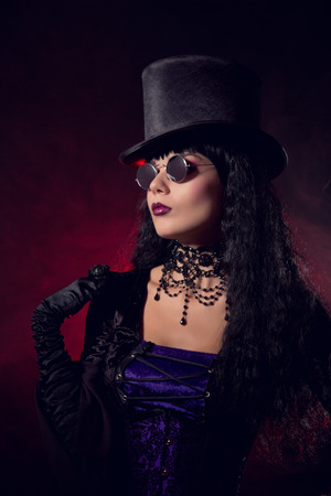 Vampire gothic girl in tophat and round eyeglasses, studio shot with smoke background  photo