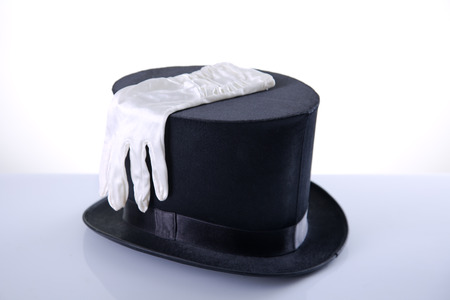 Black top hat with silk white gloves, studio shot on white background with reflection   photo