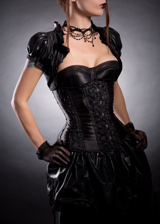 Elegant woman in Victorian style costume, studio shot on black background  photo