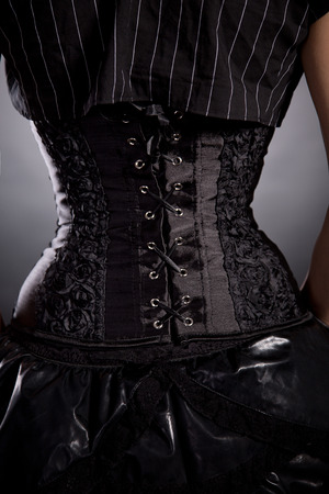 Back view of woman in black rose corset, studio shot on black background