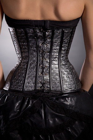 black woman lingerie: Rear view of woman in silver leather corset with stars pattern, studio shot